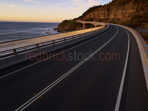 highway; highways; road; roads; ocean road; ocean roads; coast; coastal; coast road; coast roads; coastal roads; curved road; curved roads; paved road; paved roads; sealed road; sealed roads; bitumen; bituman; sunlight; sun light; daytime; daylight; cliff; cliffs; cliff face; cliff face; ocean; sea; sea water; water; wet; golden; golden sun; golden sunlight; golden sun light; golden colour; golden color; no light pole; no light poles; no street light; no street lights; modern; empty; empty road; empty roads; no car; no cars; no vehicle; no vehicles; no traffic; white line; white lines; double white line; double white lines; centre line; centre lines; guard rail; guard rails; bollard; bollards; drive; horizon; horizons; driving; low angle; low view; low viewpoint; bridge; sea cliff bridge; australia; australian; cgi; background; backgrounds; 2d cgi plate; 2d cgi plates; backplate; backplates; back plate; back plates; 2d backplate; 2d backplates; 2d back plate; 2d back plates;and; paved road; paved roads; sealed road; road; roads; sealed roads; bitumen; curve; curved; curving; curved road; curved roads; bend; bends; bending; bending road; bending roads; on-ramp; on ramp; on-ramps; on-ramps; off ramp; off ramps; off-ramp; off-ramps; morning; early morning; modern; no car; no cars; no vehicle; no vehicles; white line; white lines; single white line; centre line; centre lines; guard rail; guard rails; bollard; bollards; overpass; overpasses; underpass; underpasses; highway; highways; hwy; highway underpass; highway underpasses; bridge; bridges; street light; street lights; light; lights; traffic light; traffic lights; copyspace; copy space; textspace; text space; cement; low angle; low view; cgi; background; backgrounds; 2d cgi plate; 2d cgi plates; architecture; design; blue sky; blue skies; clear blue sky; clear blue skies;  sign; signs; signage; road sign; road signs; road signage; speed limit; speed limits; clem jones tunnel; clem jones; clem7; clem 7; clem7 tunnel; clem 7 tunnel;static; stationary; backplate; backplates; back plate; back plates; 2d backplate; 2d backplates; 2d back plate; 2d back plates; and; &; +;