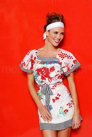 woman;girl;young woman;young woman standing againts a red background;woman smiling;woman laughing;woman looking away from camera;woman wearing a dress;headband;fashion;beautiful woman;red;person;one person