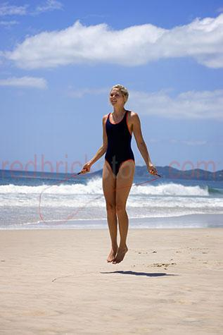 female;females;woman;women;girl;girls;lady;ladies;skipping;skip;skips;skipping rope;skipping ropes;jump;jumps;jumping;exercise;exercises;exercising;exercising on the beach;exercising at the beach;20-25 years;20 to 25 years;20-25 yrs;20 to 25 yrs;young adult;mid 20s;mid 20Õs mid twenties;25-30 years;25 to 30 years;25-30 yrs;25 to 30 yrs;health;health and fitness;health & fitness;fitness;fit;blonde;blond;blonde hair;blond hair;blue sky;blue skies;sand;sandy;ocean;sea;seas;sea water;water;wet;sporty;athletic;train;trains;training;training session;training sessions;bathers;togs;swimwear;swim wear;speedos;getting fit;keeping fit;wave;waves;cloud;clouds