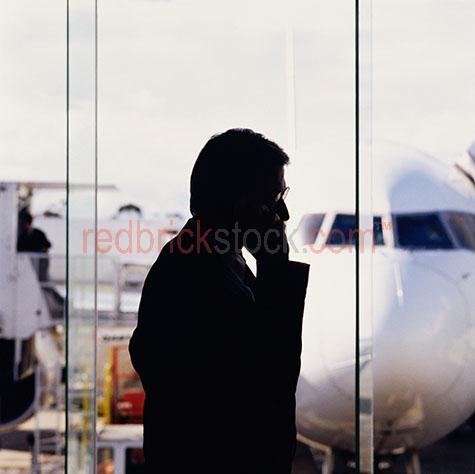 businessman;business man;travel;airport;terminal;silhouette;silhouetted;silhouettes;talking;talk;mobile phone;cell phone;communication;plane;aircraft;jumbo jet;departure;departing;working;work;executive