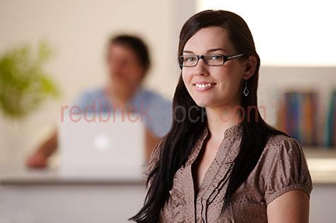 young woman in office;business;businesswoman;business woman;business women;woman smiling;smile;smiles;woman wearing reading glasses;woman wearing glasses;desk;desks