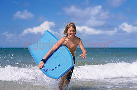 boy running surf body board boogie play playing sport happy smil