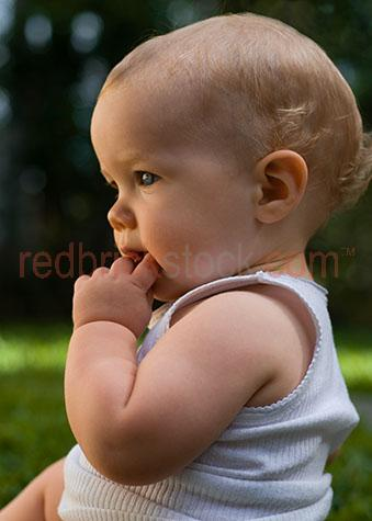 baby white singlet chewing hand in mouth young infant profile