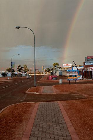 rainbow;rainbows;storm;storms;stormy;stormy weather;storm cloud;storm clouds;grey clouds;gray clouds;grey sky;grey skies;gray sky;gray skies;outback;outback australia;australian outback;outback town;outback towns;country;country town;counry towns;small country town;small country towns;coober pedy;south australia;sa;winch place;shops;shop;local shop;local shops;red dirt;dirt;road;roads;car;cars;one car;1 car;single;sign;signs;signage;street light;street lights;dark;moody