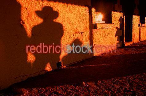 shadow;shadows;shadows of country men;country;countries;wall;walls;background;backgrounds;acubra;acubras;men in hats;men wearing hats;man in hat;long shadow;long shadows;sunset;sun set;setting sun;red dirt;red earth;red soil;outback;out back