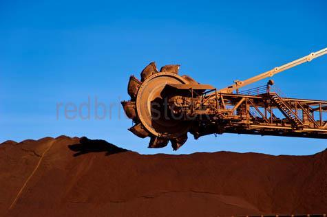 bhp;fmg;heavy industry;iron ore;mining;mine;newman;pilbara;port hedland;reclaimer;western australia;wa;australia;loading area;minerals;resources;stacker;stockpile;industry;industrial;heavy industry;mining machinery;mining equipment;day;daytime;blue sky;blue skies;outback;desert;close-up;close up