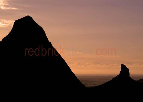 glass house mountains;mountain;mountains;mt beerwah;mount beerwah;mt coonowrin;mount coonowrin;rock face;cliff;cliffs;cliff face;cliff faces;sunrise;sunrises;sun rise;sun rising;rising sun;early morning;sunset;sunsets;sun setting;setting sun;dusk;dusks;late afternoon;golden light;golden;colour gold;color gold;sunshine coast;south east queensland;se queenslad;qld;glass house mountains;glass house mountain;nature;landscape;outdoor;outdoors;national park;national parks;backlit;backlighting;silhouette;volcanic;volcanic plug;volcanic plugs;range;ranges;mountain range;mountain ranges;mountain peak;mountain peaks;peak;peaks;caboolture;textspace;text space;copy space;copyspace