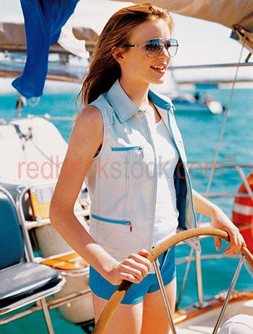 young woman;woman;lady;youth;drive;driving;boat;boats;yatch;leisure;wheel;smiling;smile;summer;relax;holiday;lifestyle;fashion;sunglasses;sunnies;glasses;sail;sailing;water;coastal;coast;relaxation;boating
