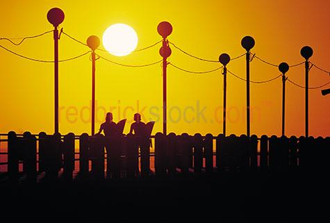 sunset;sun set;pier;orange;yellow;silhouette;silhouettes;silhouetted;people;surfers;surfer;surf;coast;beach;lifestyle;holiday;holidays;jetty;jettys;piers