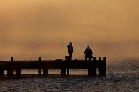 fishing;fisherman;fishermen;fishing rod;fishing rods;rod;rods;beach fishing;tackle box;tackles boxes;silhouette;silhouetted;silhouettes;pier;piers;fishing pier;fishing piers;wharf;wharfs;fishing wharf;fishing wharfs;coastal;coastal living;coastal lifestyle;ocean;sea;water;sea water;beach lifestyle;leisure;morning;early morning;early morning fishing;morning fishing;fog;foggy;father and son;father;fathers;son;sons;child;children;kids;kid;bond;bonding;father and son bonding;orange;oranges;colour orange;color orange;dawn;sunrise;sunrises;sun rise;sun rises;sunrising;sun rising;copyspace;copy space;textspace;text space
