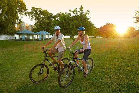 couple;young;exercise;bike;bikes;bicycle;bicycles;smile;smiling;laugh;laughing;highgate hill;west end;park;parks;ride;riding