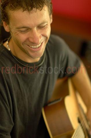 guy playing guitar;acoustic;acoustic guitar;yound guy;man;25-30 yrs old;twenty-five to thirty years old;at home;laughing;smiling;enjoying;playing guitar;leisure;friends;music;musician;guitarist;strumming