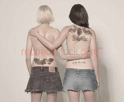 women;woman;young;youth;true love;tattoo;tattoos;tatoo;tatoos;denim;blonde;blond;brunette;ink;arm;arms;hold;holding;arms around each other;two;2;back;backs;facing away