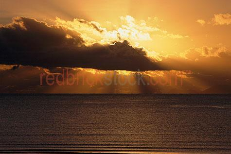 sunrise;sun rise;ocean;beach;clouds;cloud;sea;sun beam;beams;sunrays;ray;rays;glow;gold