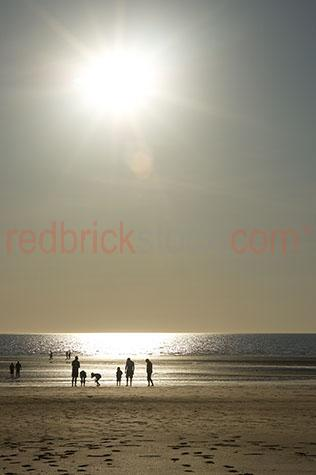 late afternoon beach scene people family sunset water ocean sun