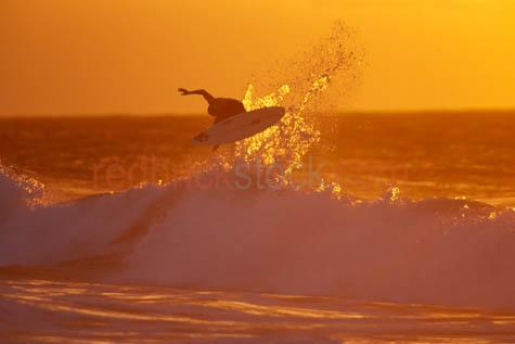 surfer getting air;surfing;surf;surfer;wave;waves;surfer in sunset;setting sun;boardrider;board rider;surf board;board;beach;beaches;off the lip;getting air;airborne;air borne;golden;golden sunset;action;sport;sports