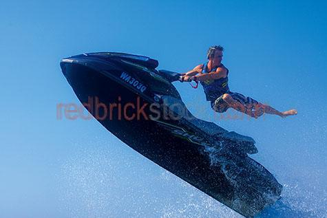 jet ski;jet skis;jetski;jetskis;jet-ski;jet-skis;watersport;watersports;water sport;water sports;jet;jets;fast;speed;summer;splash;splashes;extreme sport;extreme sports;action;jump;jumping;jumps;activity;activities;adrenaline;male;guy;man;one man;one guy;men;guys;blue;blues;colour blue;color blue;ride;riding;man riding jet ski;person;one person;seadoo;seadoos;seado;seados;blue sky;blue skies;clear sky;clear skies