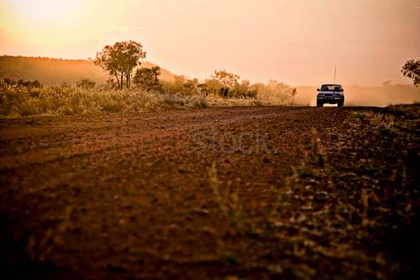 road;roads;dirt road;dirt roads;unsealed road;unpaved;gravel road;gravel roads;country road;rural road;outback;arid;dry;parched;sparse;dust;dusty;dusty road;drive;driving;car;cars;4WD;four wheel-drive;toyota;landcruiser;vehicle;vehicles;backlit;backlight;backlighting;low angle;low view;low viewpoint;sunset;sun set;sunrise;sun rise;lens flare;flare;flaring;flares;sunburst;sun burst;empty foreground;landscape;landscapes;outback;australia;australian;orange sky;sunset sky;20061101_AUST_0311