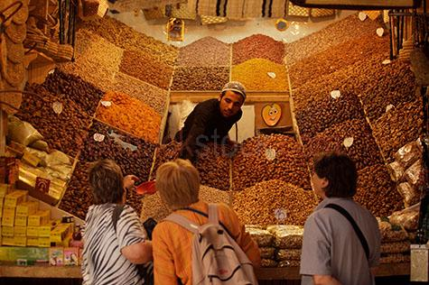 dried fruit;dried fruit seller;market trader;market;markets;street seller;marrakech;fruit;healthy;diet;diets;piles of dried fruit;customer;customers;marrakech souk;indoor market;indoor markets;assortment;assortments;morocco;africa