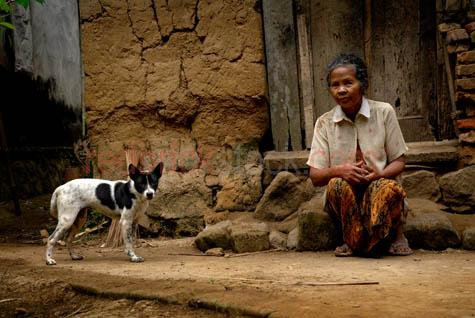 bali;balinese;man;balinese woman;indonesia;indonesian;ubud;village;old;old woman;dog;hut;with dog;dogs;villages;villager;poor;mud hut;dwelling;house sitting in front of house;sitting;steps;earth;brick;bricks;sarong;thongs;sandals;third world;asia;asian;south east asia;poverty