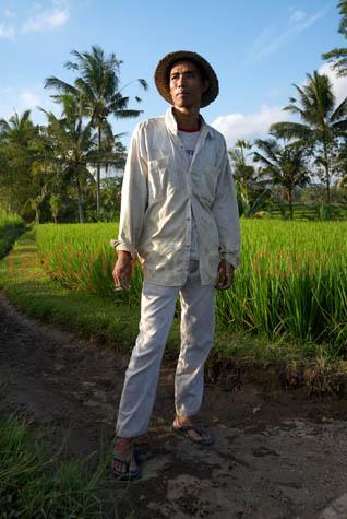 bali;balinese;man;balinese man;indonesia;indonesian;ubud;bicycle;village;villager;farmer;rice farmer;cigarette;cigarettes;smoking;hat;straw hat;coconut palms;coconut trees;coconut farmer;asia;asian;south east asia;young man;standing;field;track;path