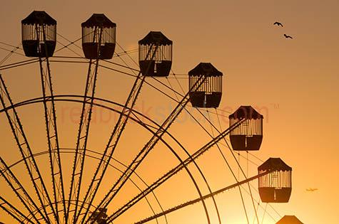 ferris wheel;amusement park;carnival;fair;carnivals;fete;ride;rides;amusement ride;amusement rides;amusement parks;silhouette;silhouetted;silhouettes;silhouetted ferris wheel;silhouetted ferris wheels;silhouetted of ferris wheel;sunset;sun setting;sunsets;sun set;sun sets;setting sun;carriage;carriages;ride;rides;skyline;sky line