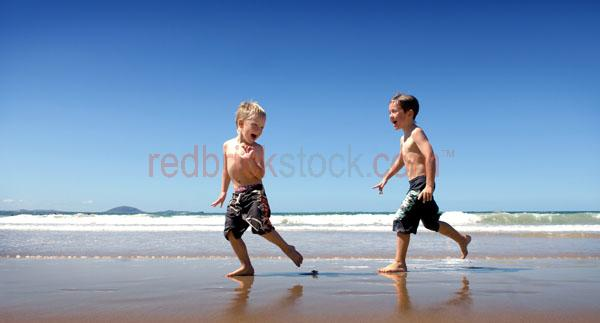 boys playing;kids at the beach;children at the beach;kids playing;kids running;having fun;kids having fun;kids laughing;children having fun;beach;running on the beach;chasing;kids chasing each other;children chasing each other;boys running;young boys playing;boy;boys;togs;swimmers