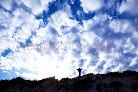 man beach;young man beach;one man;young guy;men;beaches;dune;dunes;standing;standing on dune;standing in dunes;arms outstretched;arms up;freedom;free;nature;silhouette;silhouettes;silhouette;in silhouette;silhouetted;silhouette of man;sky;skies;sky beach;sky sand dune;sky sand dunes;cloud;clouds;cloudy sky