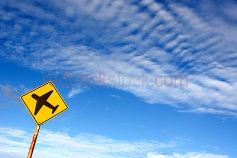airplane sign against blue sky;plane sign;planes;plane;sign;signage;traffic sign;traffic signage;blue sky white clouds;conceptual