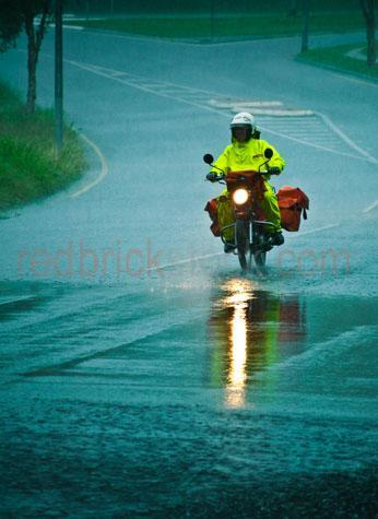 postman;postmen;postal;postal worker;postal workers;postie;posties;mailman;mail man;mail carrier;mail carriers;mail;delivering mail;mail delivery;delivery;courier;mail courier;mail couriers;motorbike;motorbikes;bike;ride;riding;riding motorbikes;motorbike in rain;motorbikes in rain;weather;wet weather;wet conditions;wet;rain;rainy;raining;pouring rain;rain shower;rain showers;drizzle;drizzling;storm;stormy;overcast;evening;late afternoon;failing light;dim;dark;dim light;road;roads;wet road;wet roads;road conditions;dangerous road conditions;hazardous;hazard;street;streets;work;working;job;jobs;occupation;occupations;australia post;dismal;uncomfortable;cool tones;cool tone;reflection;reflections;textspace;text space;copy space;copyspace