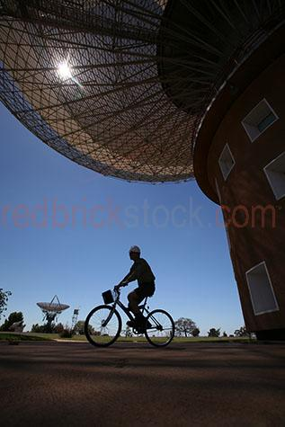 dish;the dish;dishes;observatory;observatories;parabolic;antenna;antennas;parkes;nsw;new south wales;australia;aus;oz;radiothermal telescope;radiothermal telescopes;radio thermal;radio;radio telescope;radio telescopes;telescope;astronomy;astronomer;movable dish;movable dishes;stars;star;moon;moons;moon landing;nasa;apollo 11;broadcast;broad cast;galaxy;galaxies;universe;bike;bikes;bicycle;bicycles;worker;workers;person;people;one person;one man;one guy;single figure;riding bike;riding bikes;riding bicycle;riding bicycles;silhouette;silhouettes;silhouetted;hard hat;hard hats;helmut;helmuts;blue sky;blue skies;clear sky;clear skies