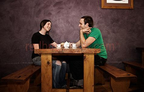 Couple in cafe;couple laughing;couple drinking tea;couple smiling;young couple;couple sitting at table;couple holding hands;cafe dining;dine;two people;laugh;laughing;smile;smiling;table;tea;couple drinking tea;drink;social;socialising;socializing