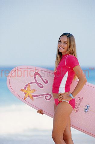 young;girl;teen;teenager;girls;youth;teens;teenagers;surf;surfboard;surfboards;surfer;surfers;pink;swimwear;swim wear;smile;smiling;looking at camera;beach;beaches;coastal;lifestyle;coast;summer