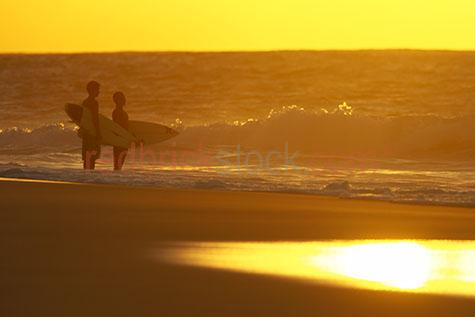surf;surfer;wave;waves;ocean;surfing;surfboard;surf board;surfers;sea;water;orange;yellow;sunset;sun set;sunrise;surfboards;guy;guys;man;men;two people;silhouette;silhouetted;silhouettes