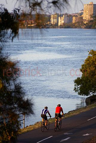 cycle;cycling;brisbane river;two people riding bikes;riding a bike;two people cycling along brisbane river;north point;exercising;exercise;bicycle;bicycles;cycling;cyclists