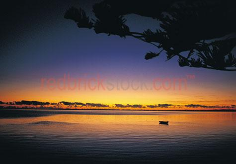 dingy moored dinghy snrise silhouette silhouetted ocean water be