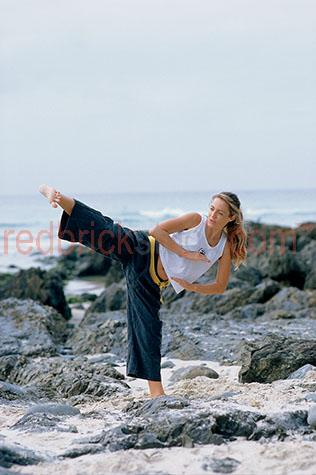 girl;girls;woman;women;kick;kicking;karate;martial arts;self defence;beach;rocks;coastal;practice;practicing;training;instructor;kung fu;aikido;tae kwon do