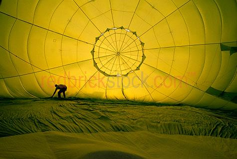 man hot air ballon inside yellow space inflate inflating balloon