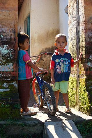 boy;boys;child;children;kid;kids;young boy;young boys;bali;balinese;indonesia;indonesian;asia;asian;native;natives;local;locals;looking at camera;people;person;two boys;2 boys;pair;pairs;look;looks;looking;bike;bikes;push bike;push bikes;bicycle;bicycles;doorway;doorways;door way;door ways;outside;outdoor;outdoors